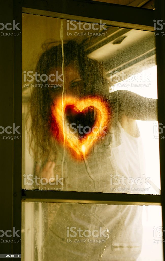 Woman Drawing Heart Symbol on Window royalty-free stock photo