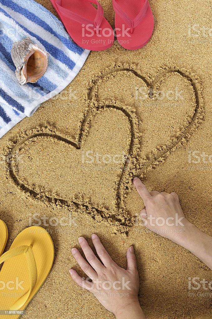 Woman drawing joined hearts in sand stock photo