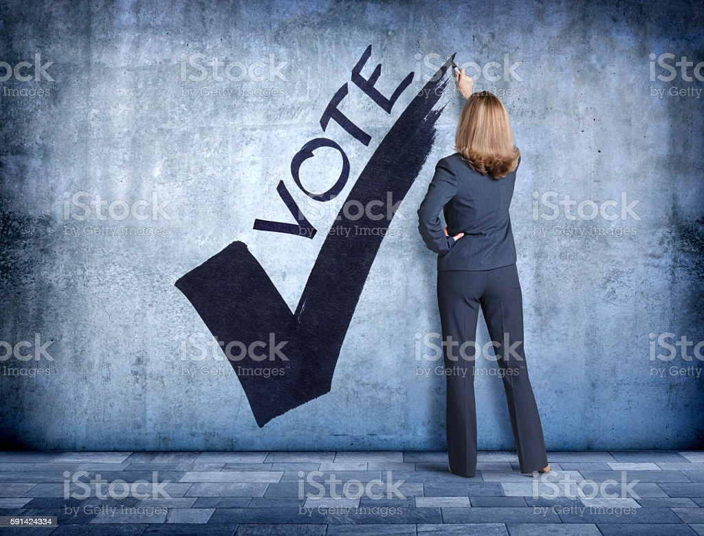 Woman Draws Large Check Mark Encouraging People To Vote stock photo