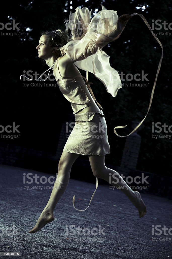 Woman Dressed as a Fairy and Jumping, Toned stock photo