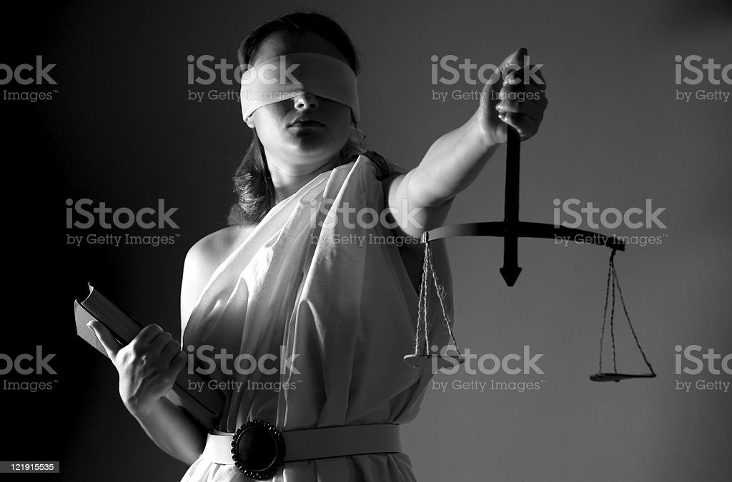 A woman dressed as justice with scales and blindfold stock photo
