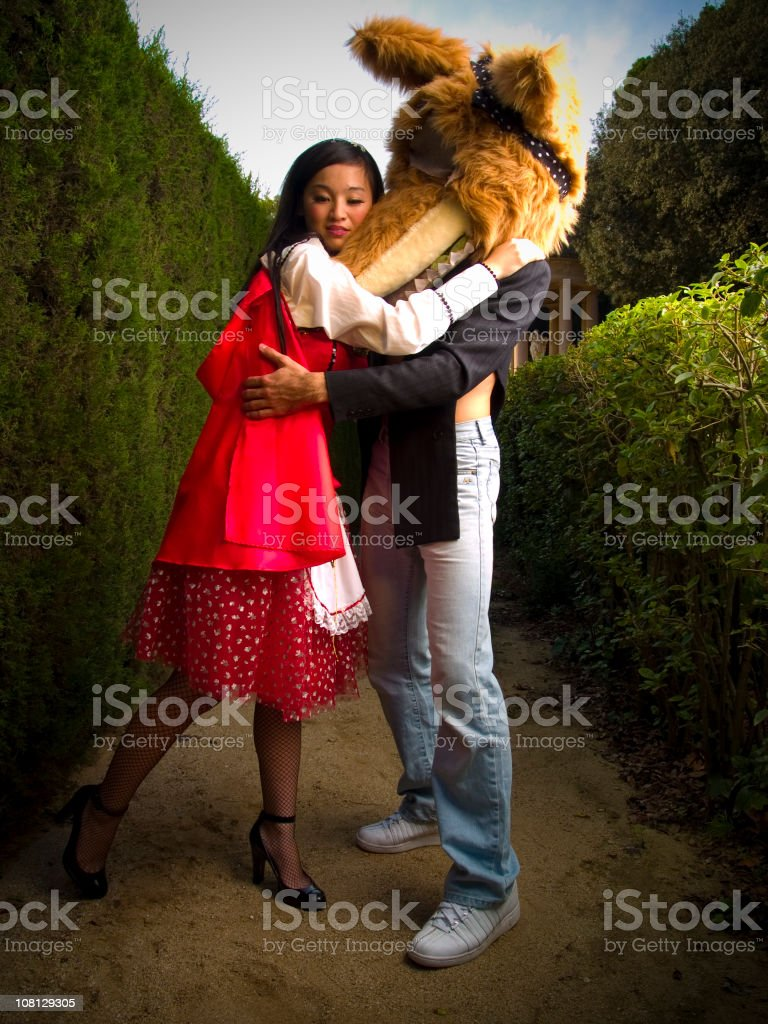 Woman Dressed as Red Riding Hood Hugging Wolf royalty-free stock photo