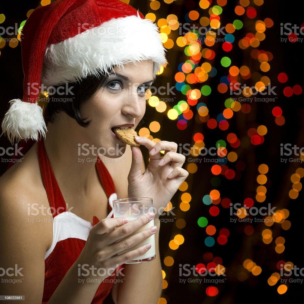 Woman Dressed as Santa Eating Cookie royalty-free stock photo