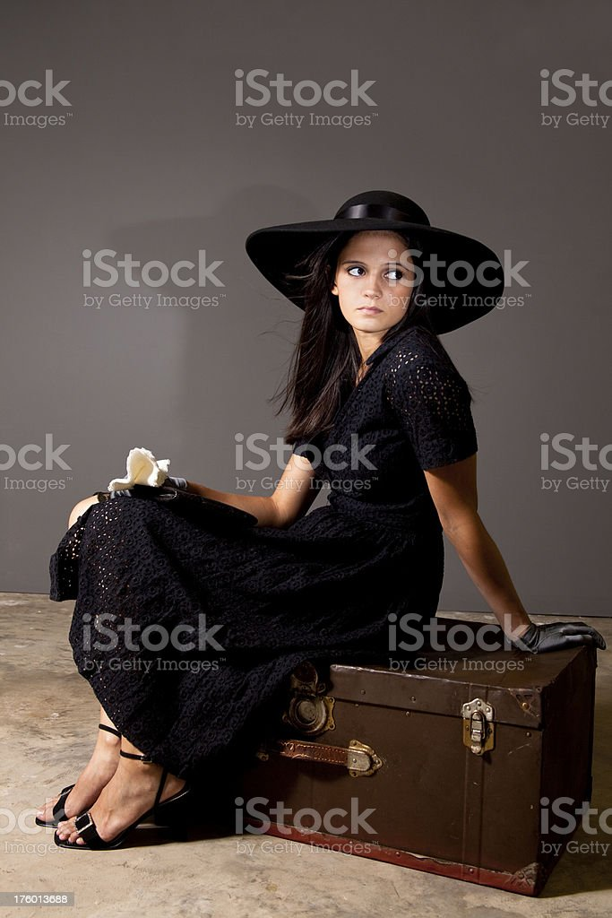 Woman dressed in 1930s attire sitting on antique trunk royalty-free stock photo