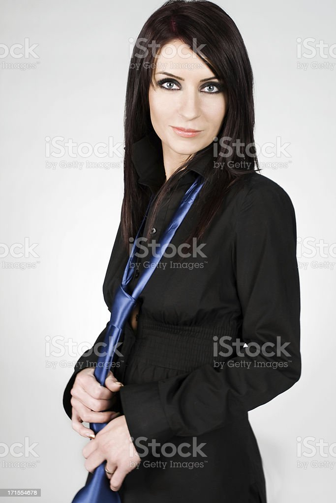 A woman dressed in all black, while wearing a blue tie royalty-free stock photo