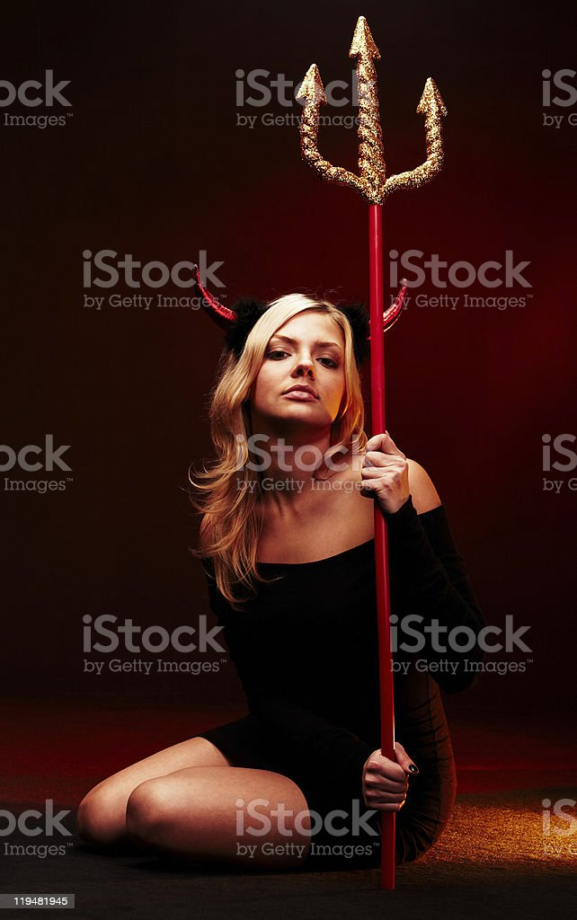 Woman dressed in devil costume holding a trident stock photo