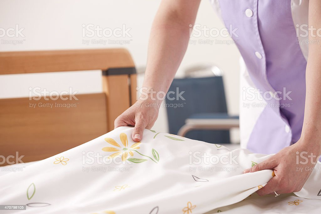 Woman dressed in lavender arranging sheets and making bed stock photo