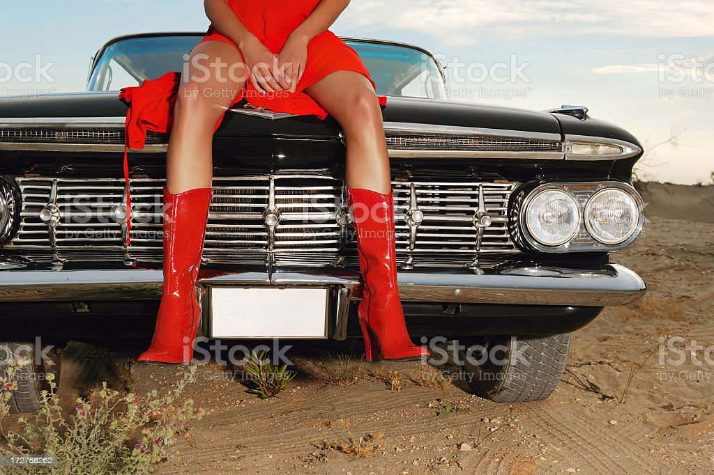 Woman dressed in red sitting atop a black car royalty-free stock photo