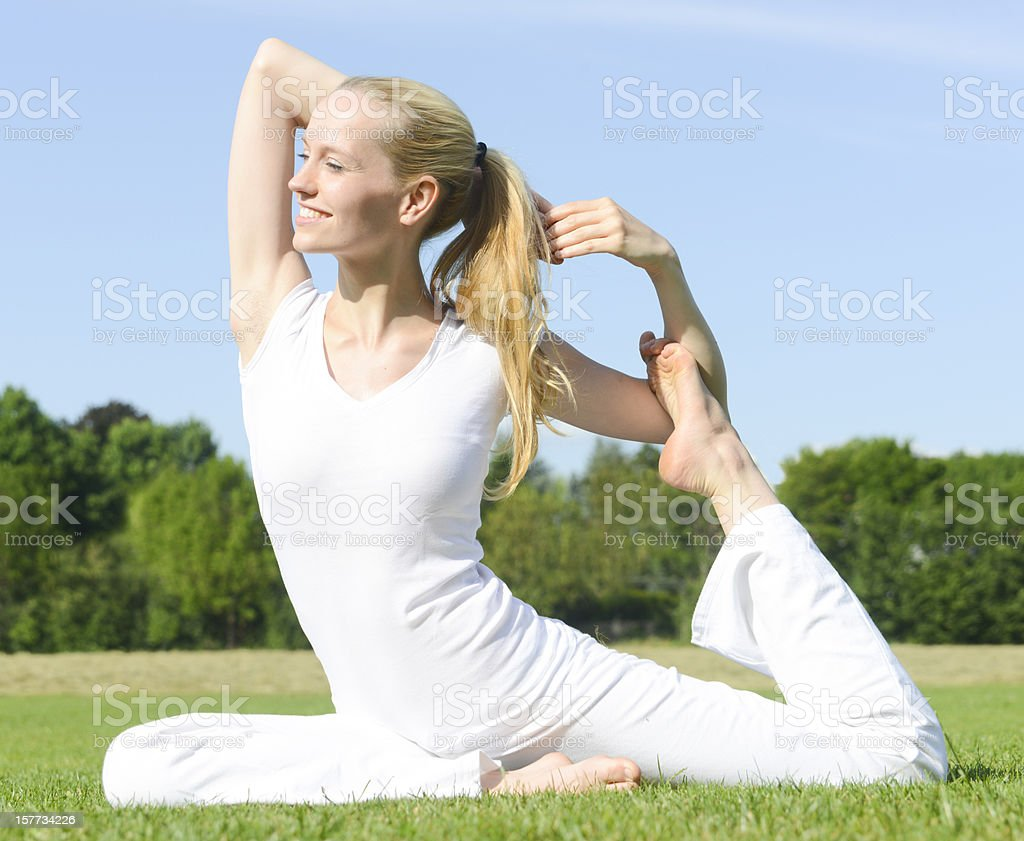 woman dressed in white doing yoga outside on green grass stock photo
