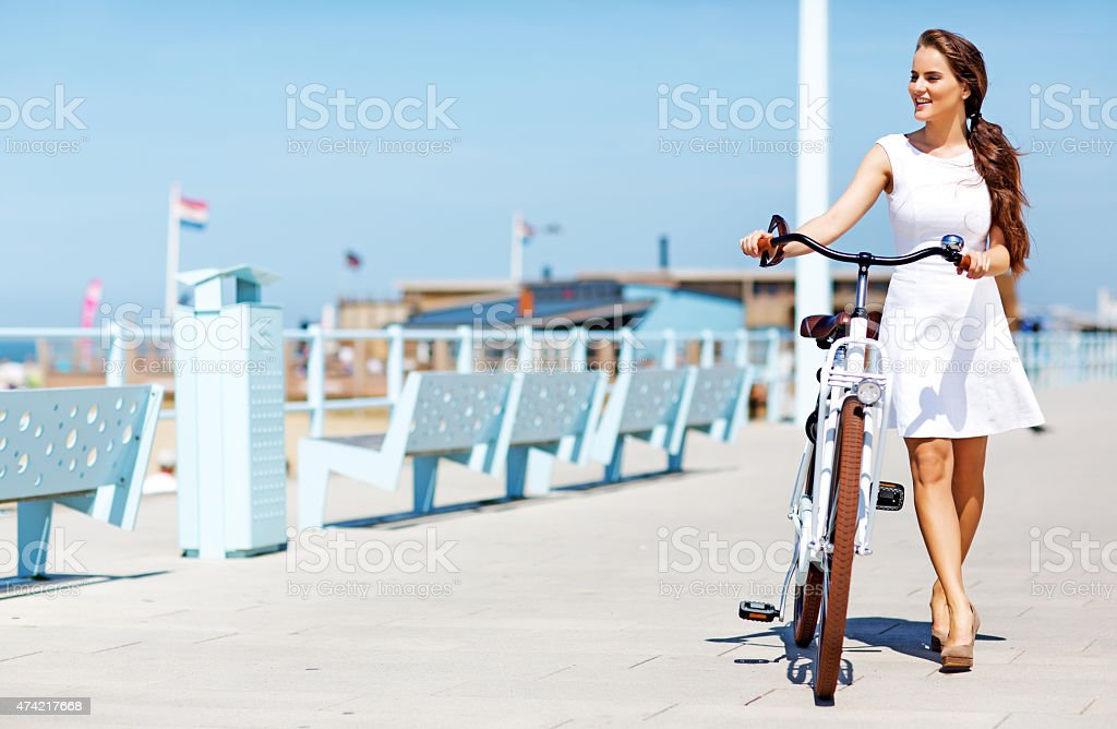 woman dressed in white  holding white bike walking near North sea stock photo