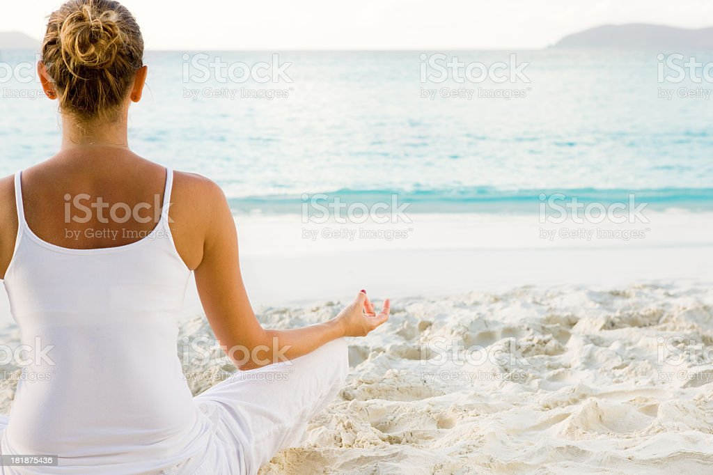 woman dressed in white meditating on the Caribbean beach royalty-free stock photo