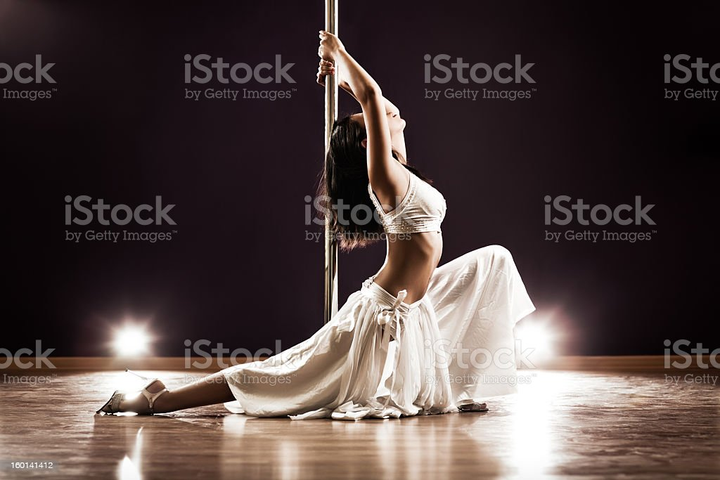 Woman dressed in white pole dancing stock photo