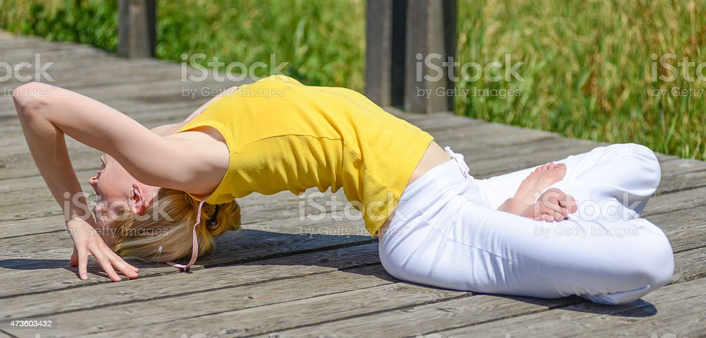 woman dressed in yellow doing yoga outside stock photo