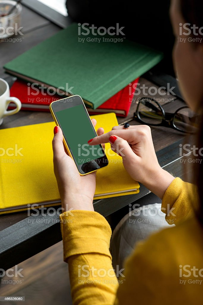 Woman dressed in yellow using her smartphone stock photo