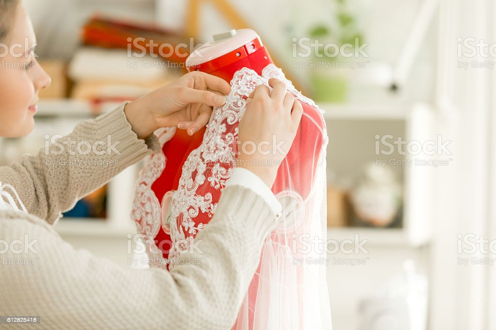 Woman dressing a tailor dummy mannequin stock photo