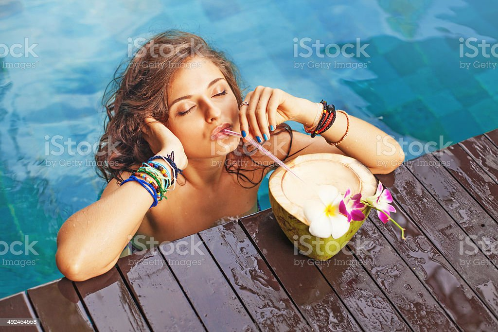 Woman drinking a coconut cocktail with closed eyes stock photo