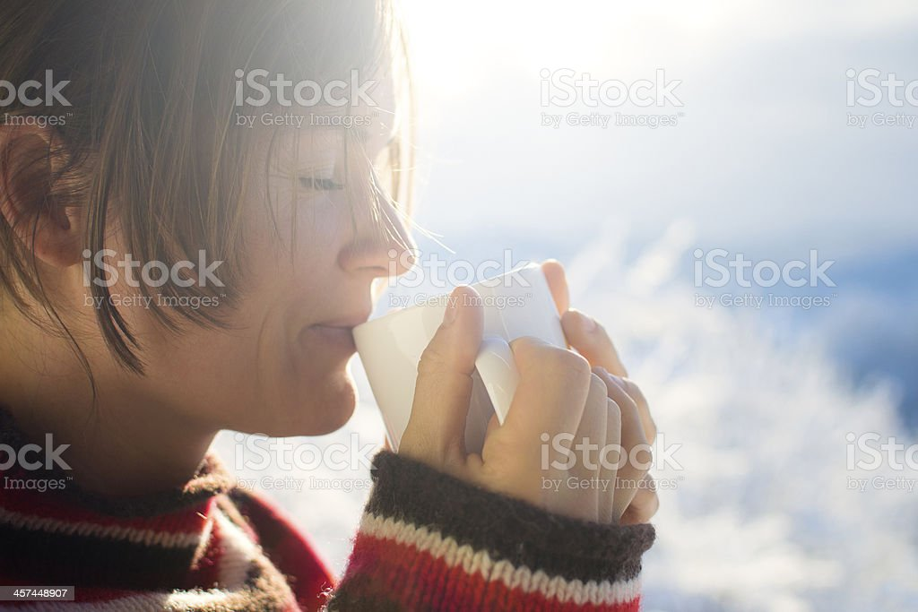 Woman drinking a hot drink while wearing a sweater stock photo
