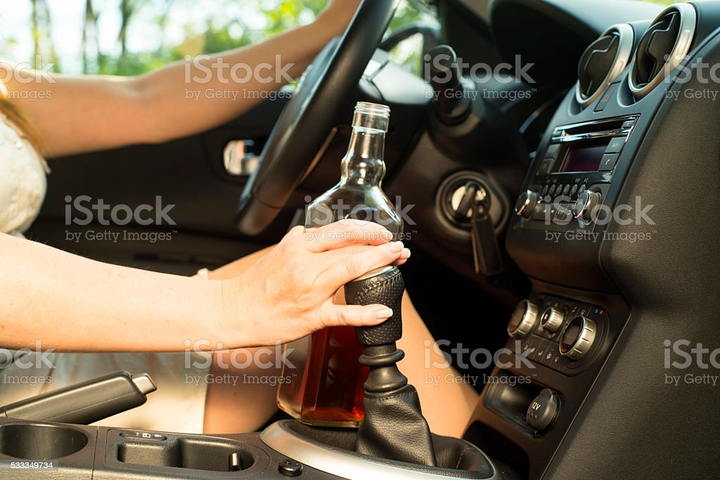 Woman drinking alcohol in the car. stock photo