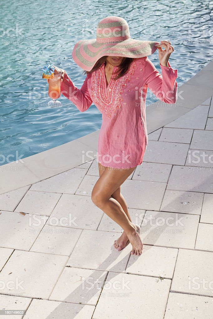Woman drinking and dancing by pool royalty-free stock photo