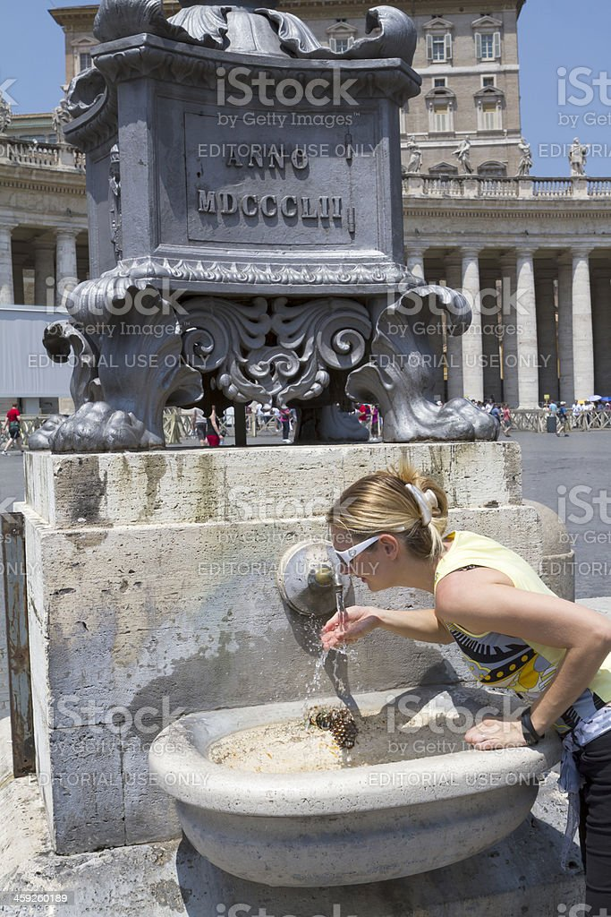 Woman drinking at a fountain in St Peter Square, Rome royalty-free stock photo
