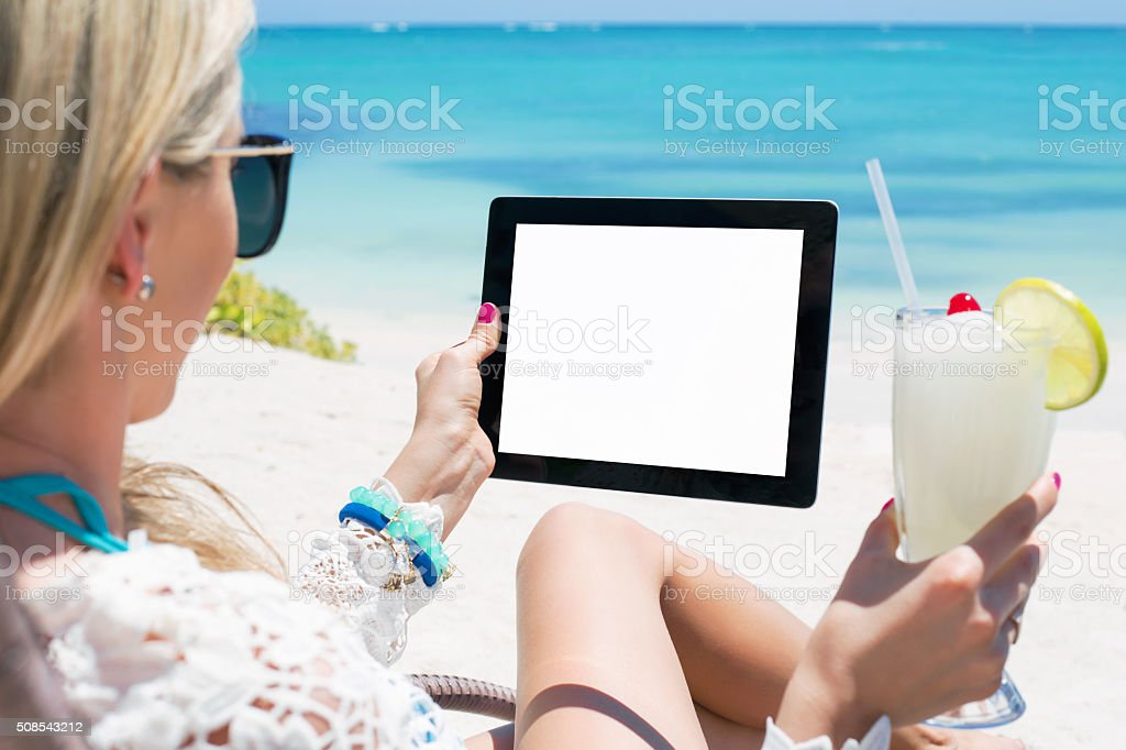 Woman drinking cocktail and holding tablet computer on the beach stock photo