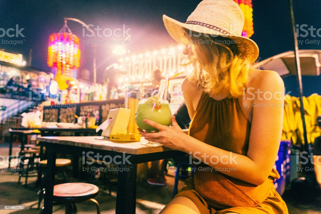 Woman drinking cocktail at night stock photo