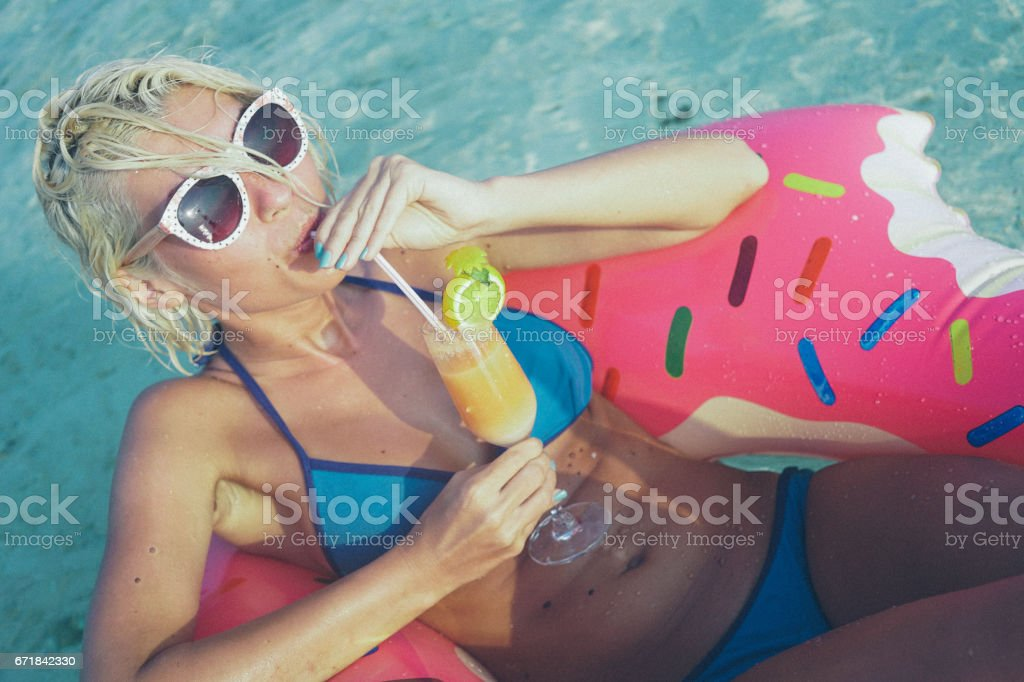 Woman drinking cocktail in the ocean, Maldives stock photo