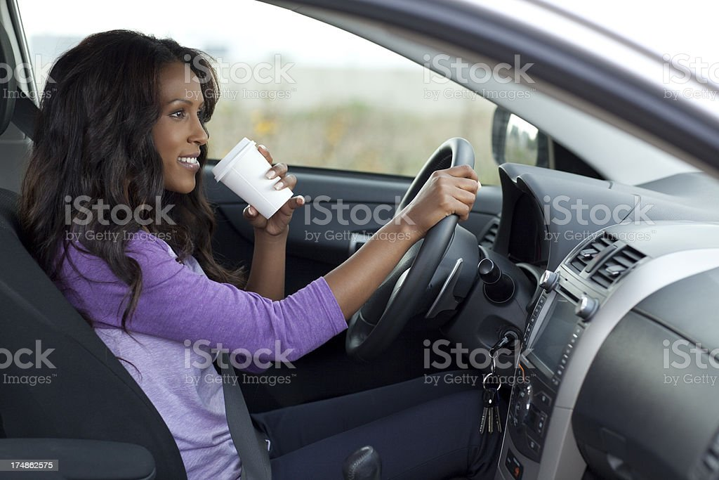 Woman drinking coffe while driving. stock photo