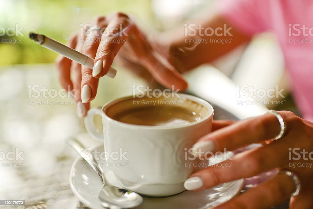 Woman drinking coffee and smoking in outdoors cafe royalty-free stock photo