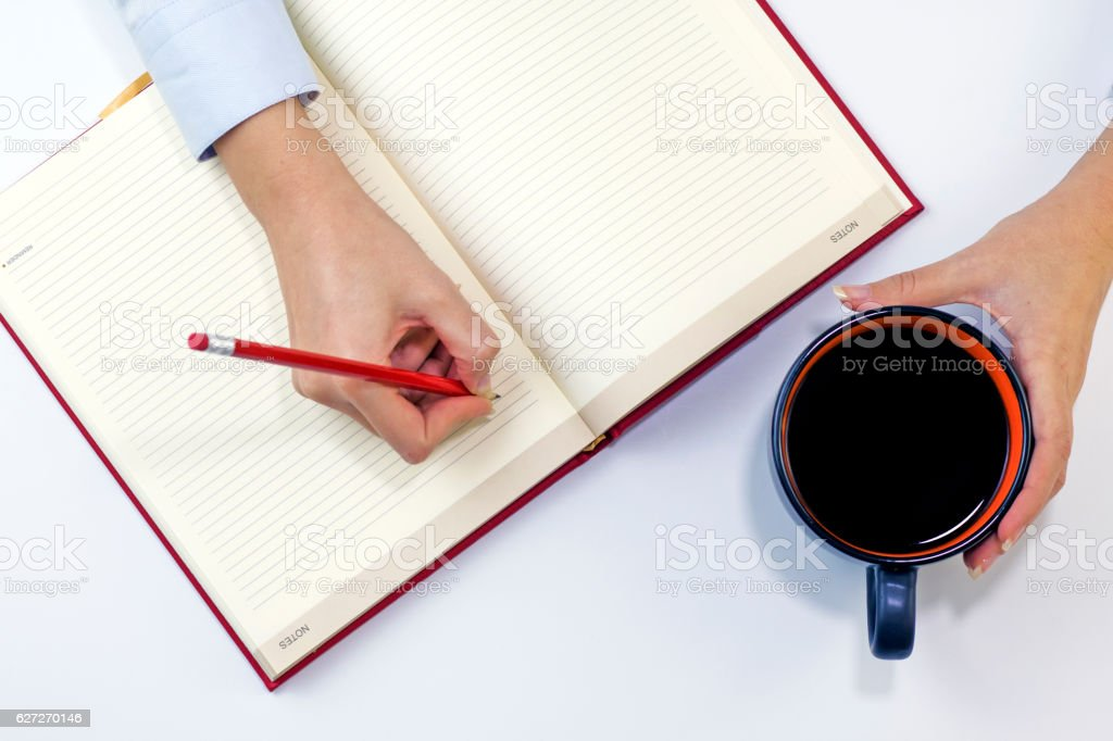 Woman drinking coffee and writing a diary note stock photo