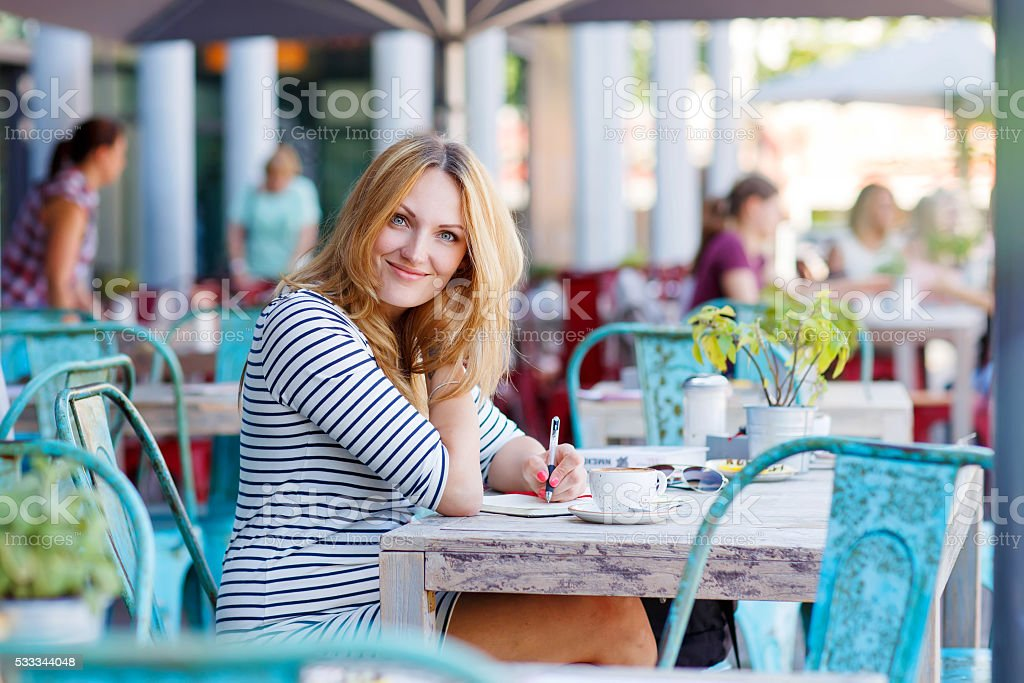 Woman drinking coffee and writing notes in cafe stock photo