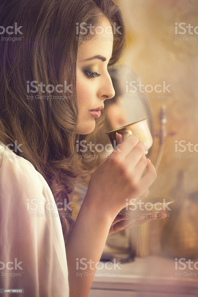 woman drinking coffee from a gold coffee cup royalty-free stock photo