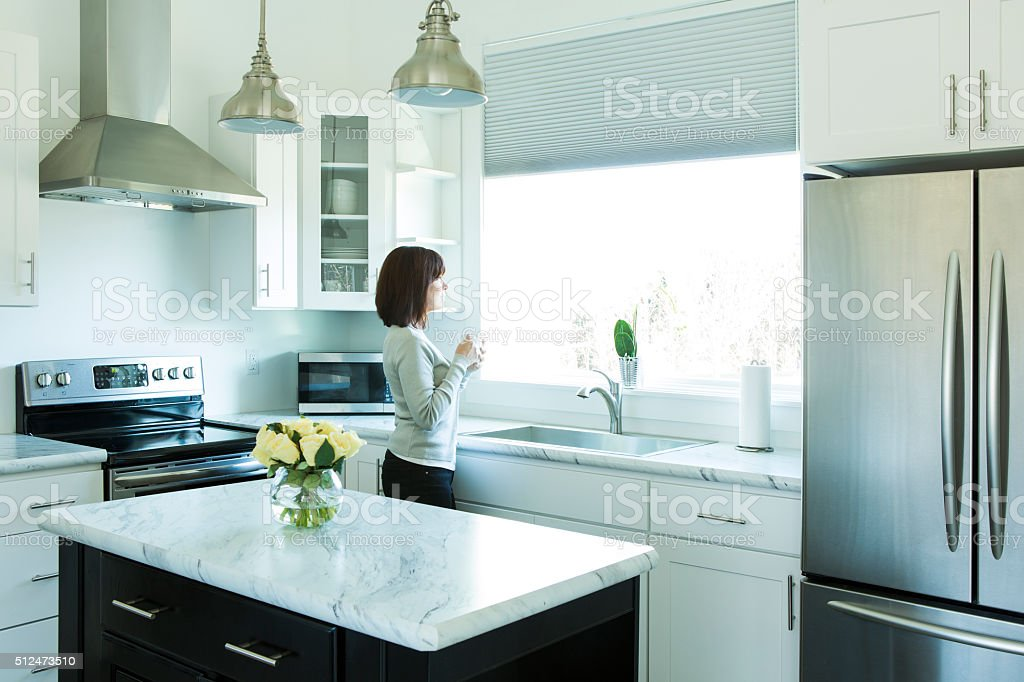 Woman Drinking Coffee in a Modern Kitchen stock photo