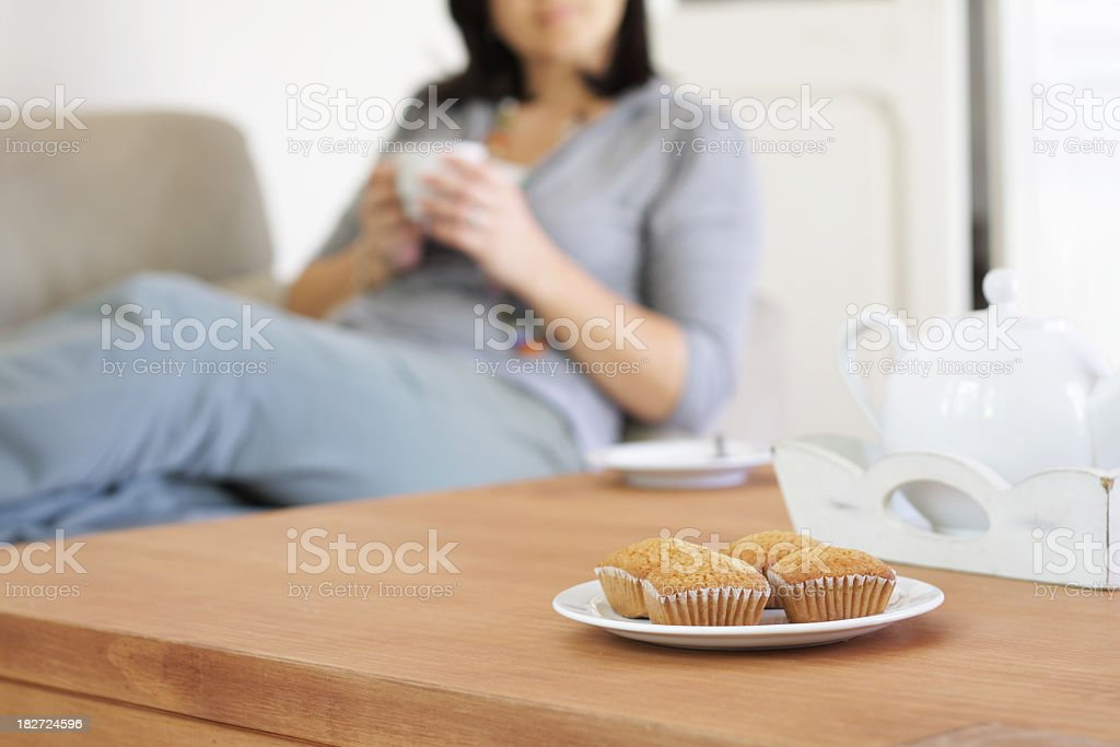 Woman drinking coffee in a sofa with muffins at foreground royalty-free stock photo