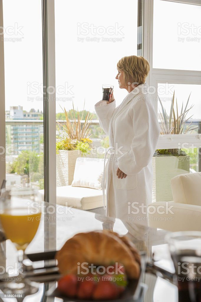 Woman drinking coffee in bathrobe stock photo