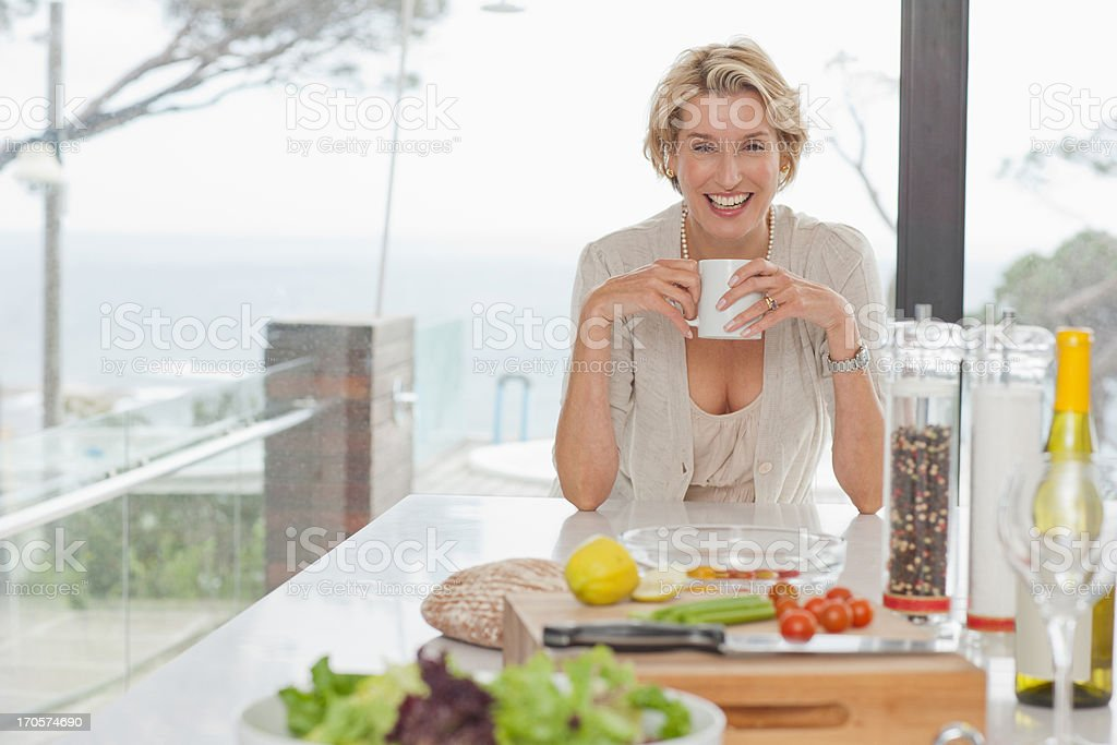 Woman drinking coffee in kitchen stock photo