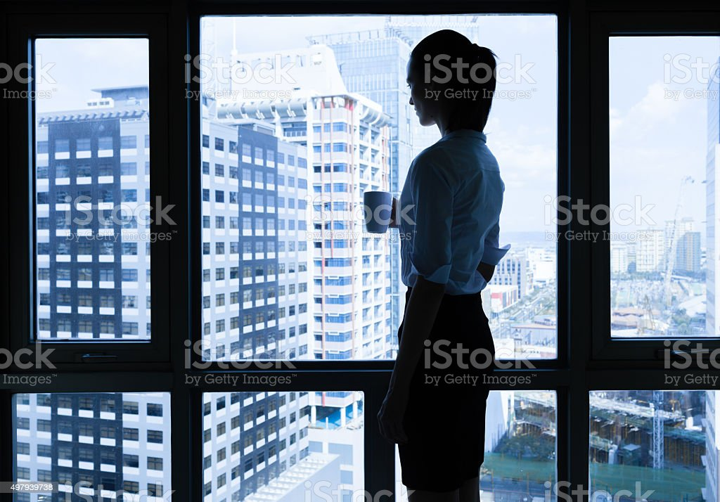 Woman drinking coffee in the office stock photo