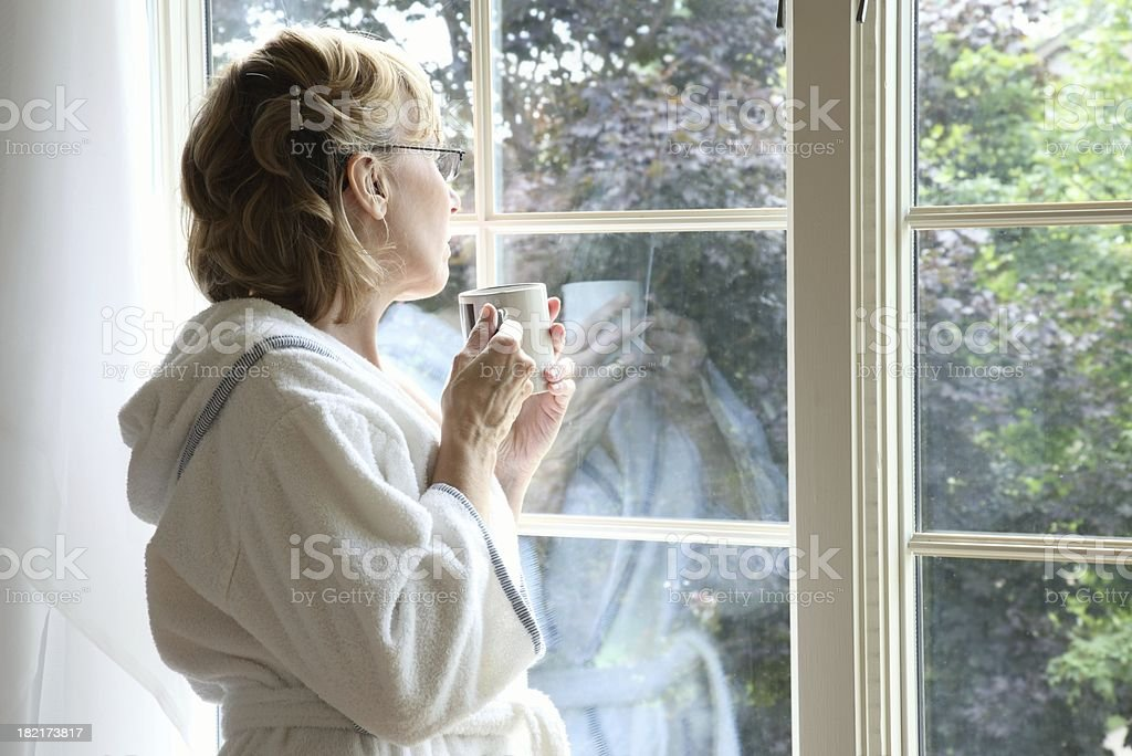 Woman Drinking Coffee Looking Out Window stock photo