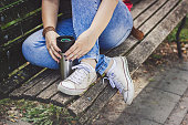Woman drinking coffee on a bench in park