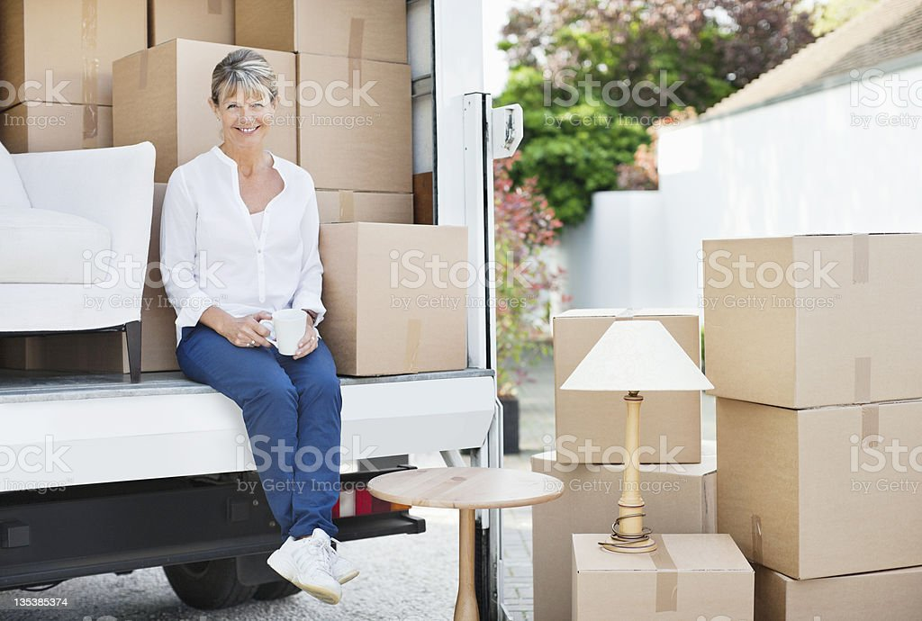 Woman drinking coffee on back of moving van royalty-free stock photo