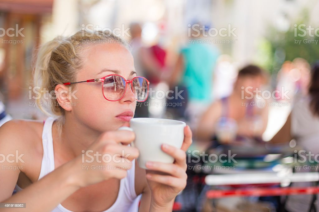 Woman drinking coffee outdoor on street. stock photo