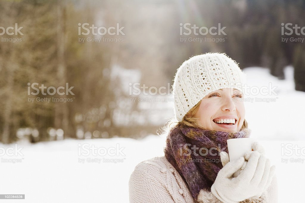 Woman drinking coffee outdoors in snow stock photo