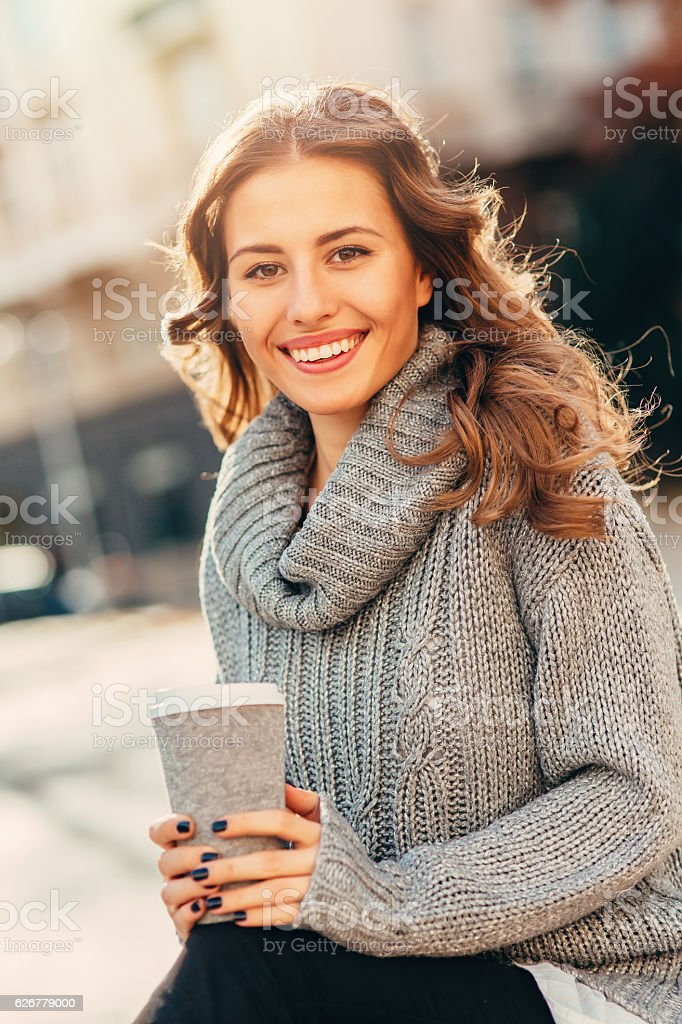 Woman drinking coffee outdoors stock photo