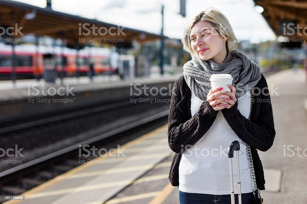 Woman drinking coffee while she waiting for the train stock photo