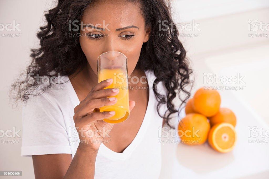 Woman drinking fresh orange juice at kitchen. stock photo