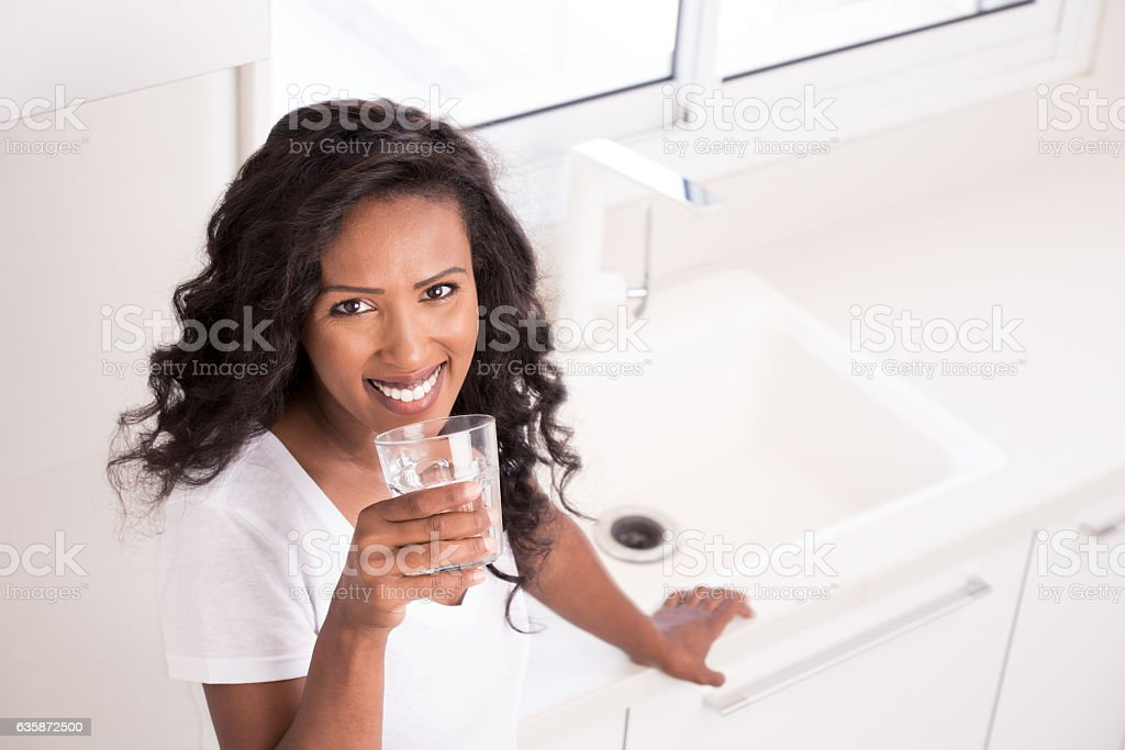 Woman drinking fresh tap water. stock photo