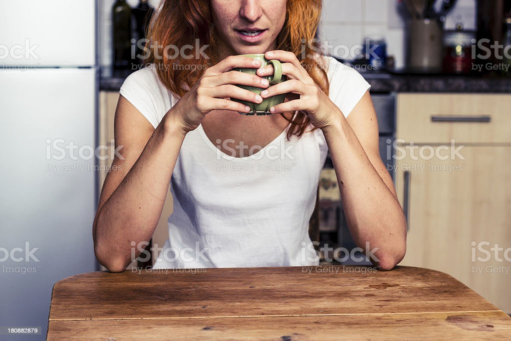 Woman drinking from cup in her kitchen royalty-free stock photo