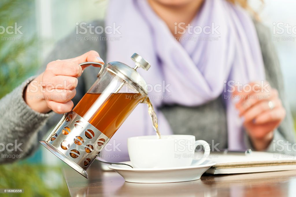 woman Drinking Herbal Tea at table stock photo