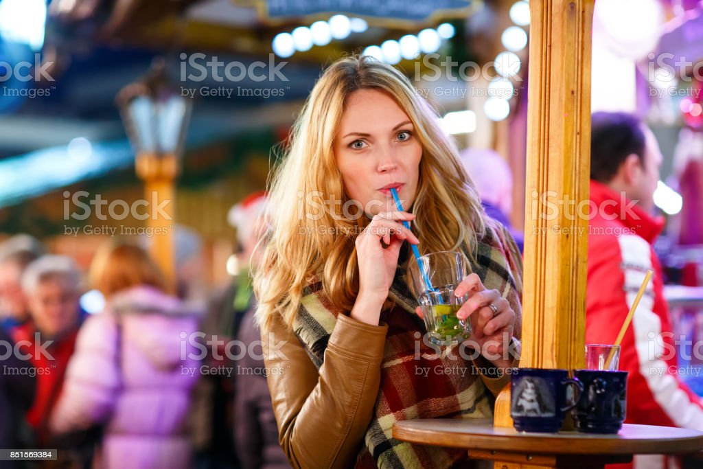 woman drinking hot punch on German Christmas market. stock photo