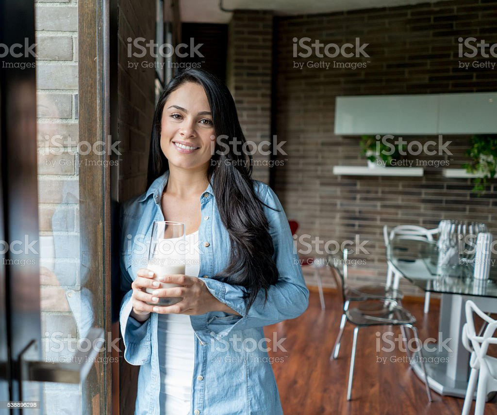 Woman drinking milk at home stock photo